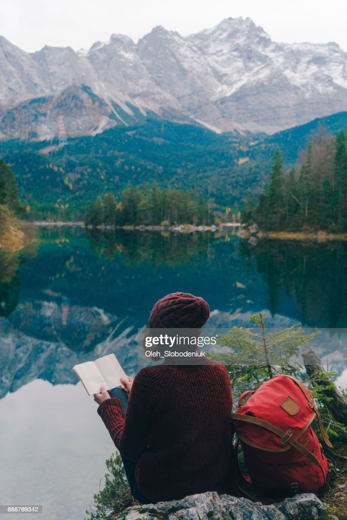 Frau liest auf dem Hintergrund der malerischen Blick auf den Eibsee See in Alpen : Stock-Foto