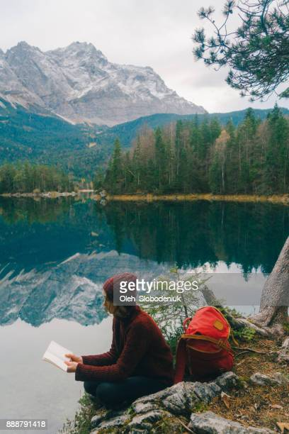 Woman reading on the background of  scenic view of Eibsee lake in Alps