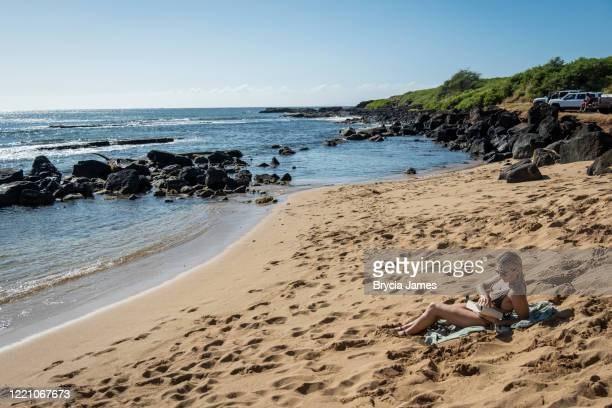 woman reading on the beach at salt pond park - brycia james stock pictures, royalty-free photos & images