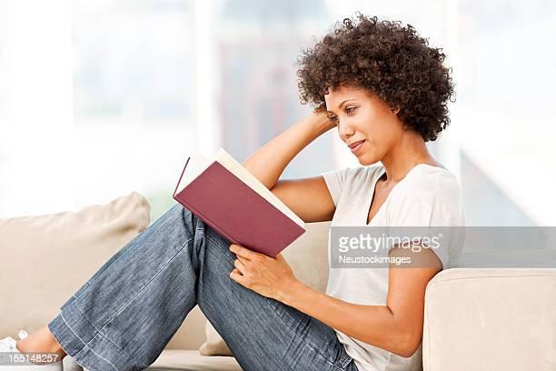 Femme lisant sur un canapé