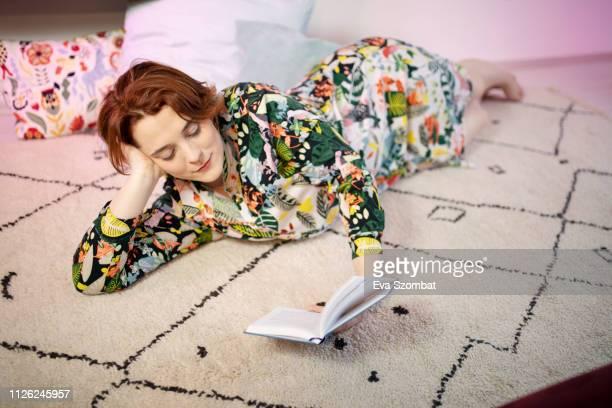 woman reading on the floor - literatur stock-fotos und bilder
