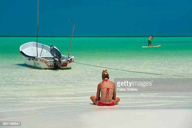 woman reading on the sea shore, holbox, mexico - isla holbox fotografías e imágenes de stock