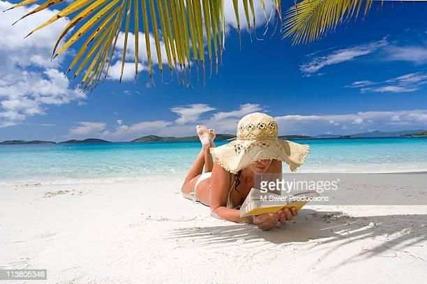 woman reading on tropical beach - acostado boca abajo fotografías e imágenes de stock