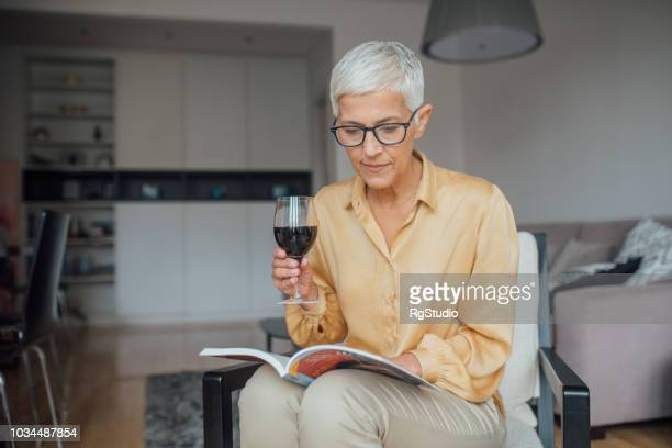 woman reading over a glass of red wine - glass magazine stock photos and pictures