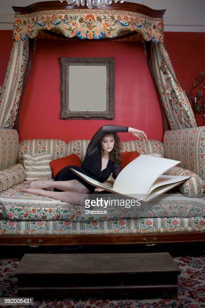 Woman reading oversized book on sofa in ornate living room