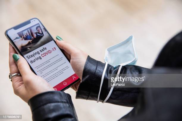 woman reading pandemic covid-19 news on mobile phone - article stock pictures, royalty-free photos & images