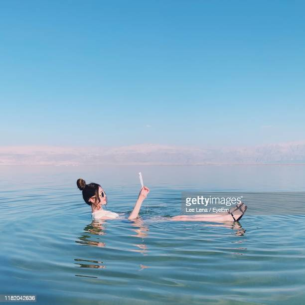 woman reading paper while floating in sea against blue sky - israeli woman stock pictures, royalty-free photos & images