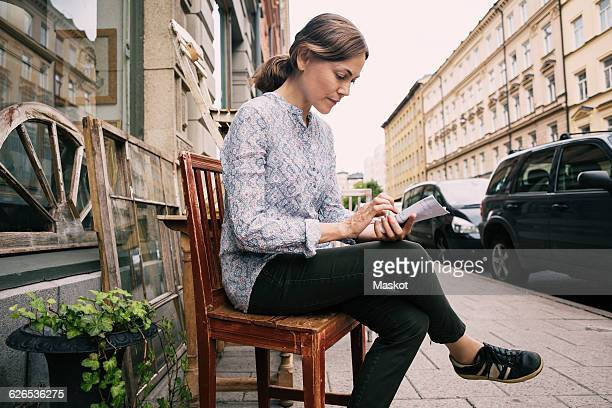 Woman reading paper while sitting on chair against store in city