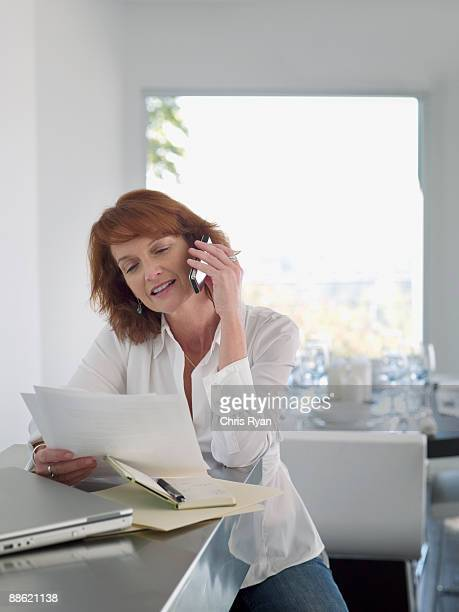 woman reading papers and talking on cell phone - older redhead stock pictures, royalty-free photos & images