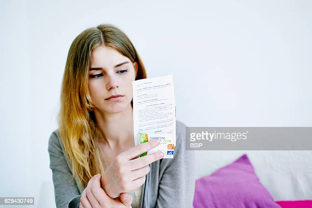 Woman reading paroxetine instruction sheet