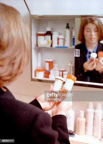 Woman reading prescription medication in bathroom