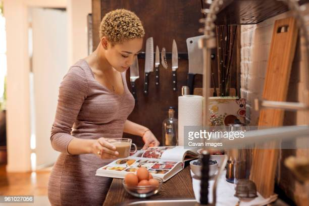 woman reading recipe book while holding tea cup in kitchen - caderno de receitas - fotografias e filmes do acervo