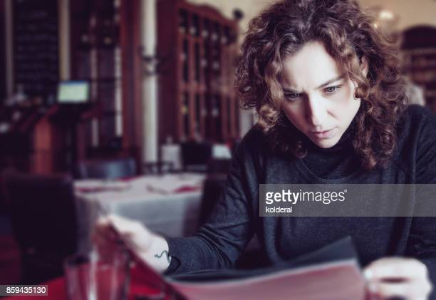 woman reading restaurant menu looked surprised by the prices - expense stock pictures, royalty-free photos & images