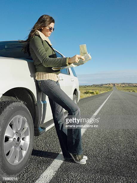 Woman reading road map by car on highway