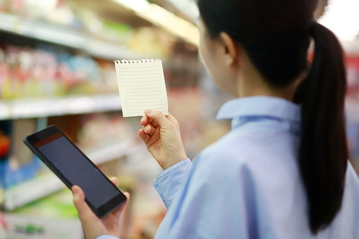 Woman reading shopping list with digital tablet in supermarket - gettyimageskorea