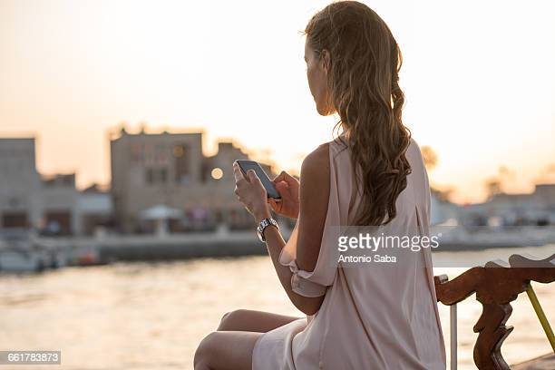 Woman reading smartphone texts on boat at Dubai marina, United Arab Emirates