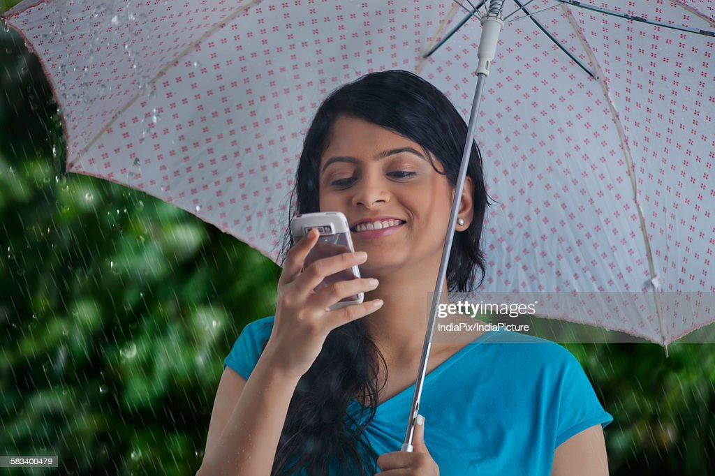 Woman reading sms on mobile phone : Stock Photo