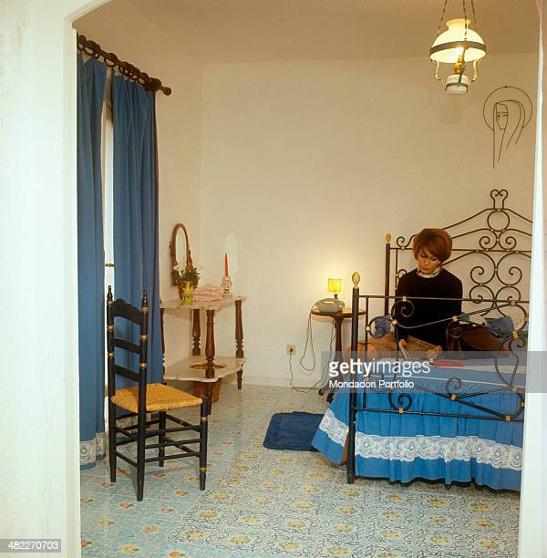 A woman reading something in a room of the Punta Rossa Hotel San Felice Circeo 1960s