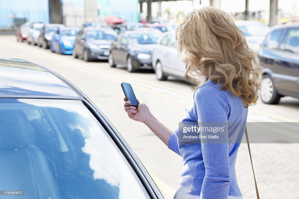 Woman Reading Text Near Line Of Cars Stock Photo | Getty Images