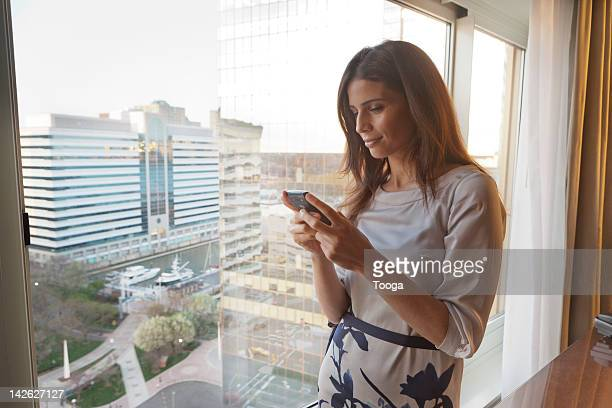 Woman reading text on phone with cityscape