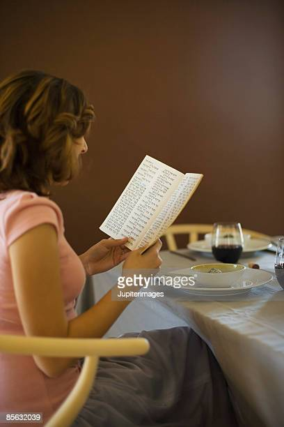 woman reading the haggadah at seder family ritual - passover seder stock pictures, royalty-free photos & images
