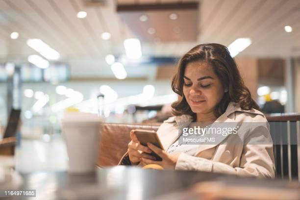 Mulher que lê a notícia em seu telefone esperto