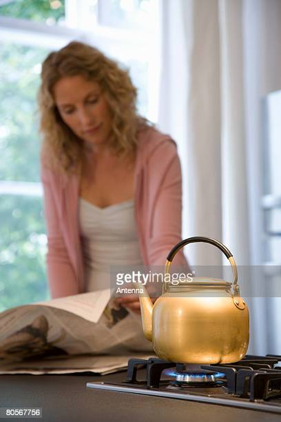 A woman reading the newspaper while waiting for a kettle to boil