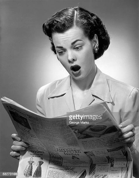 woman reading the newspaper with look of surprise - donna mezzo busto bianco e nero foto e immagini stock