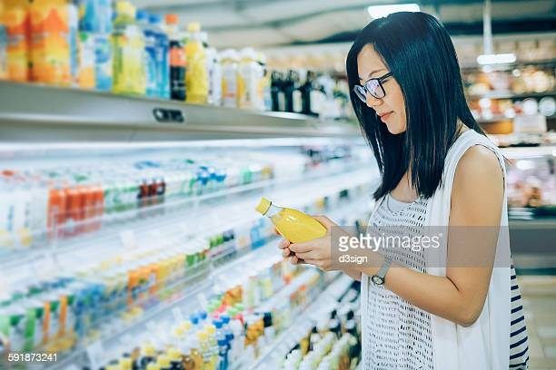 Woman reading the nutrition label on a beverage