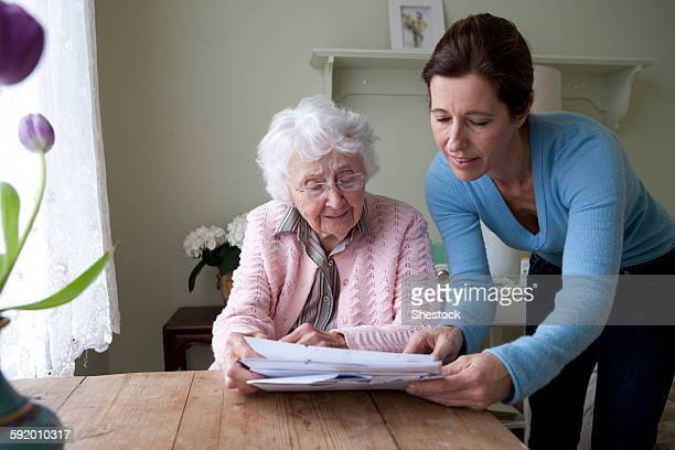 woman reading to mother at table - caseiro - fotografias e filmes do acervo