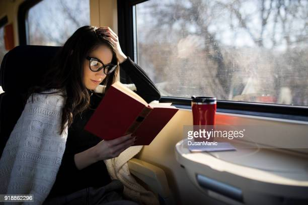 woman reading while traveling with the train commuter journey sitting - reading stock pictures, royalty-free photos & images
