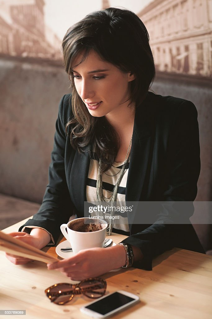 Woman reading with cup of coffee in cafe : Foto stock