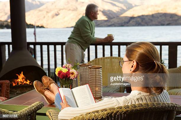 Woman reading with man outdoors