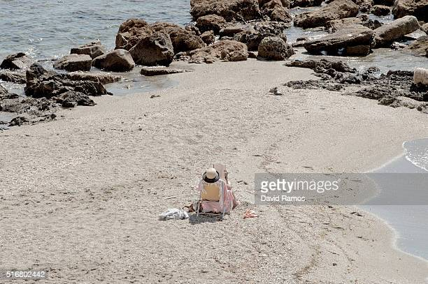 A woman reads a book as she sunbathes on the beach on March 17 2016 in Benalmadena Spain Spain is Europe's top destination for British expats with...