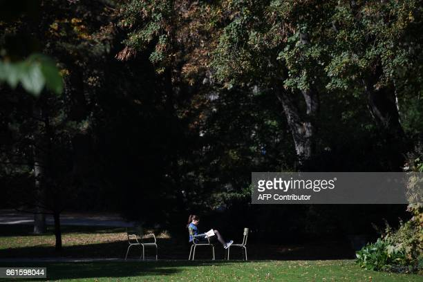 A woman reads a book at the Jardin du Luxembourg in Paris on October 15 2017 during unusually warm autumnal temperatures / AFP PHOTO / CHRISTOPHE...