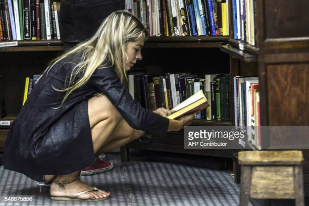 A woman reads a book at the Medellin Book Fair on September 13 2017 The Fair runs from September 10 to 17 / AFP PHOTO / Joaquin SARMIENTO