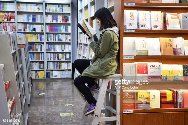 A woman reads a book in a bookstore in Beijing on November 7 2017 / AFP PHOTO / Greg Baker
