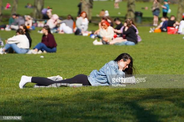 Woman reads a book in Hyde Park, Leeds , on 29 March 2021.