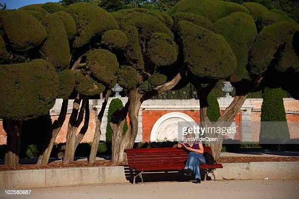 A woman reads a book in the Plaza del Parterre a part of the famous Parque Del Retiro in Madrid on May 20 2010 in Madrid Spain Madrid is a big...