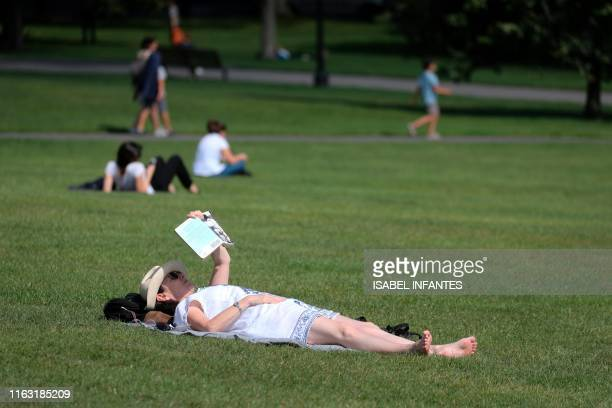 A woman reads a book lying in the grass in the sunshine on Primrose Hill in Regent's Park in London on August 22 2019