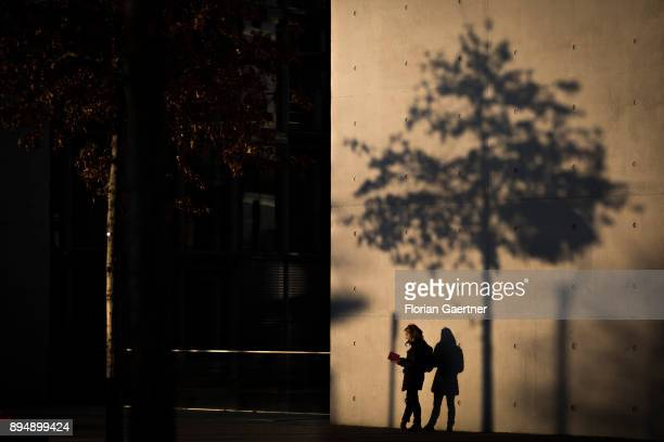 A woman reads a book next to a house facade and the shadow of a tree on December 18 2017 in Berlin Germany