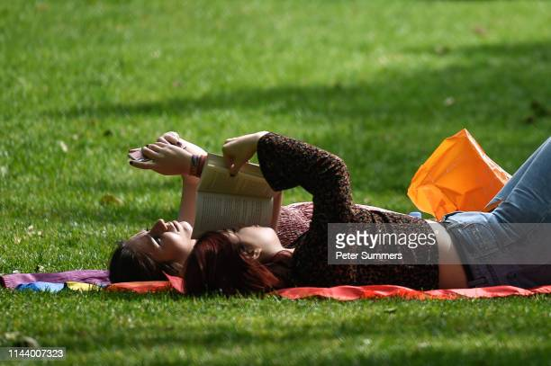 A woman reads a book next to her friend who is on her phone while relaxing in the sunshine in St James's Park on May 15 2019 in London England...