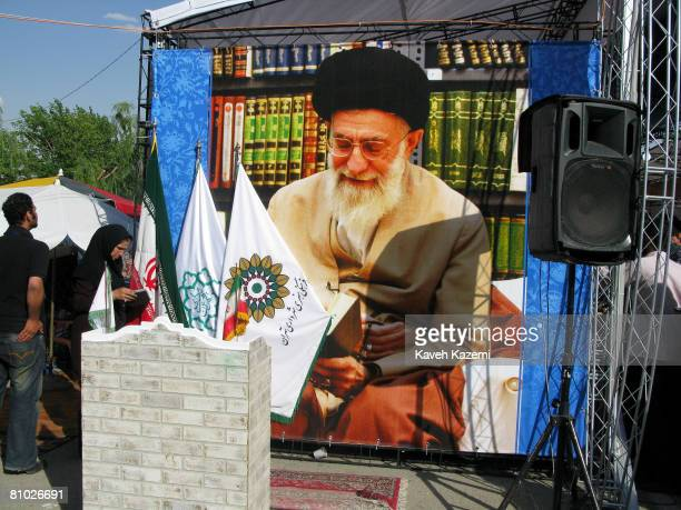 A woman reads a book next to the picture of Ayatollah Ali Khamenei outside at the 21st Tehran International Book Fair on the city's congregational...
