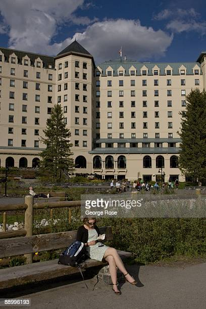 A woman reads a book on a park bench outside the Fairmont Chateau Hotel in this 2009 Lake Louise Canada summer afternoon landscape photo