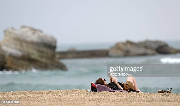 A woman reads a book on the beach in Biarritz on April 15 2015 AFP PHOTO / GAIZKA IROZ