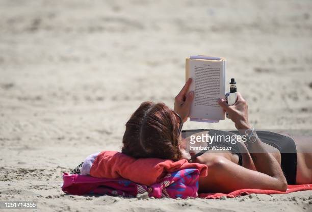 Woman reads a book on the beach on June 24, 2020 in Weymouth, United Kingdom. The UK is experiencing a summer heatwave, with temperatures in many...