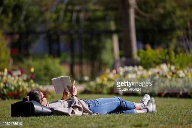 Woman reads a book on the grass in Hyde Park in the Spring sunshine in London on April 23, 2021. - Under the relaxing of the Covid-19 rules,...