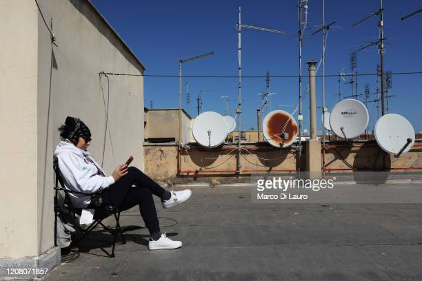 A woman reads a book on the roof of her building during lockdown on March 23 2020 in Rome Italy As Italy extends its nationwide lockdown to control...