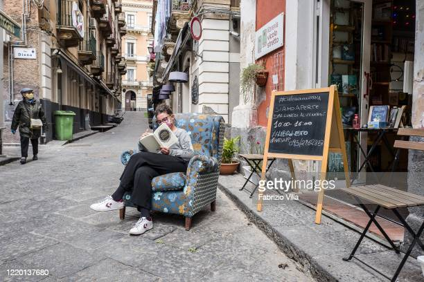 A woman reads a book outside the Vicolo Stretto bookshop following the ministerial decree that allowed the resumption of activities as part of the...