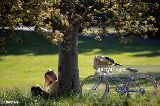 Woman reads a book under a tree in Hyde Park on May 21, 2020 in London, United Kingdom. This week temperatures reached 28 degrees celsius in the UK,...